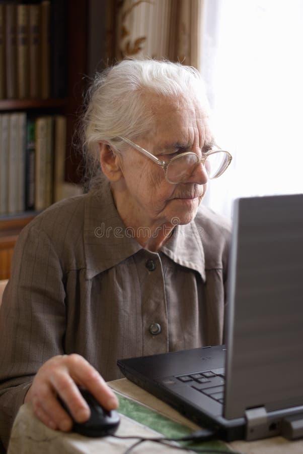 Donna maggiore con il computer portatile immagini stock libere da diritti