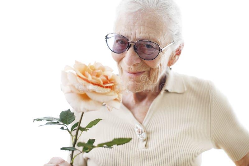Donna maggiore con il fiore fotografia stock