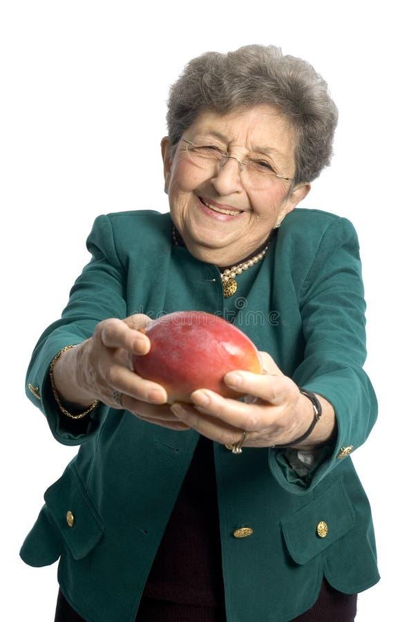 Donna maggiore con il mango fotografia stock