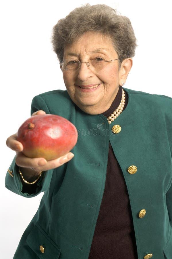 Donna maggiore con il mango fotografia stock libera da diritti