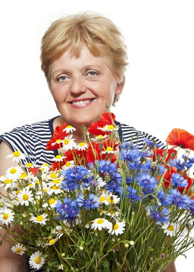 Donna maggiore con il mazzo di fiori fotografia stock libera da diritti