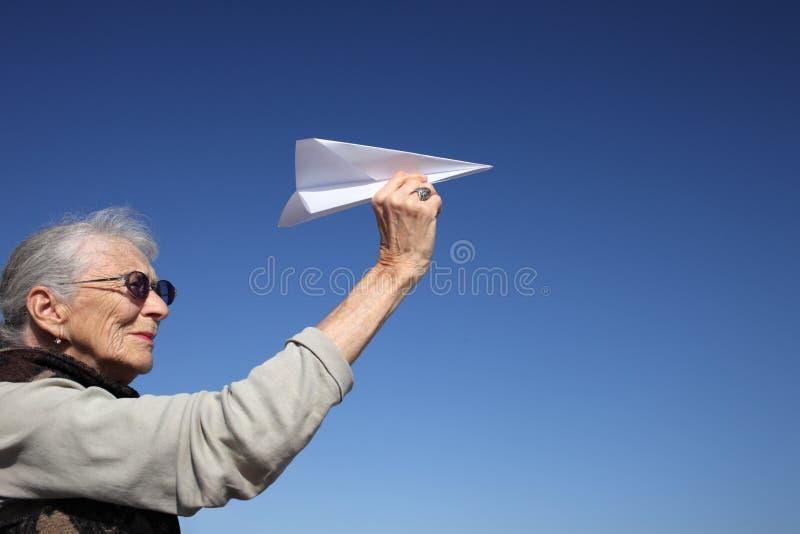 Donna maggiore con l'aereo di carta immagini stock