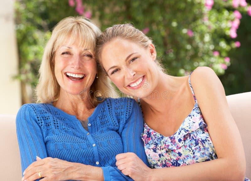 Donna maggiore con la figlia adulta che si distende nel paese immagini stock