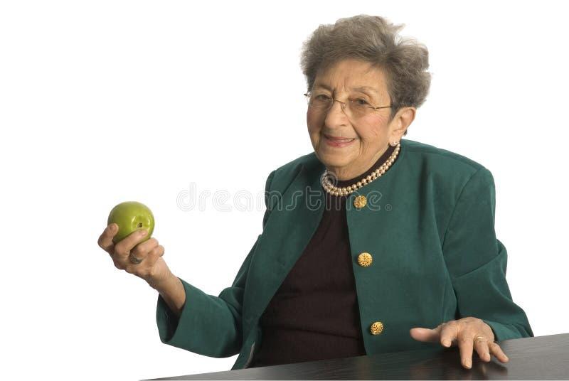 Donna maggiore con la mela immagine stock