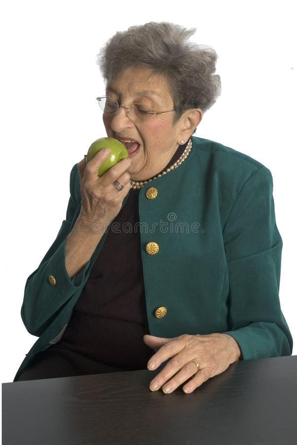 Donna maggiore con la mela fotografia stock