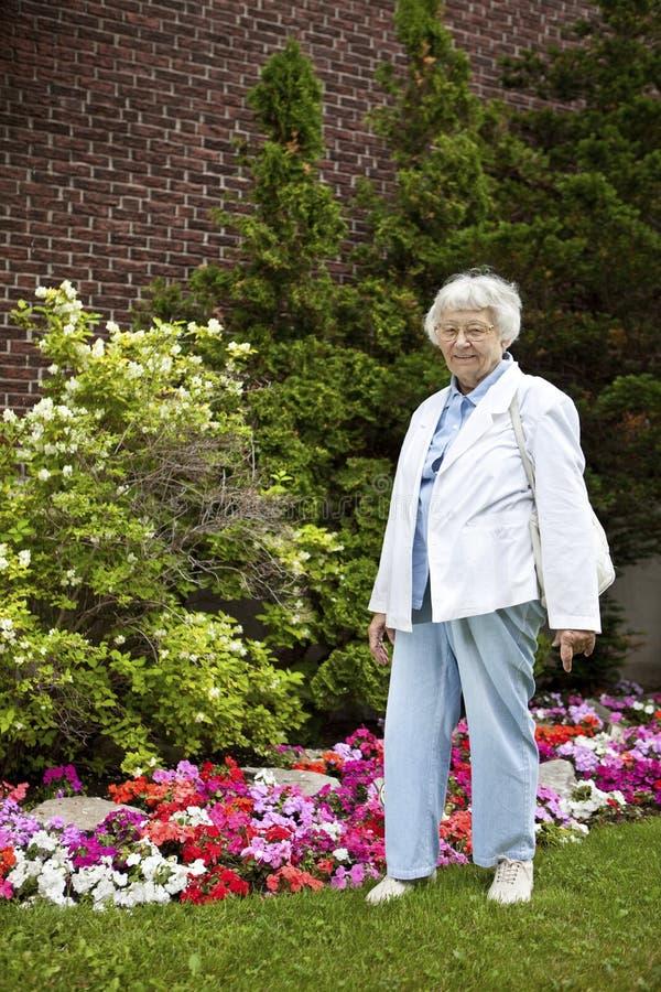 Donna maggiore con la priorità bassa del giardino fotografie stock