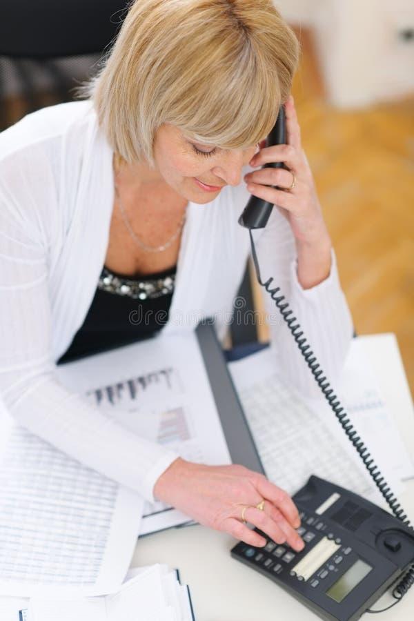 Donna maggiore di affari che fa le chiamate di telefono all'ufficio fotografia stock libera da diritti