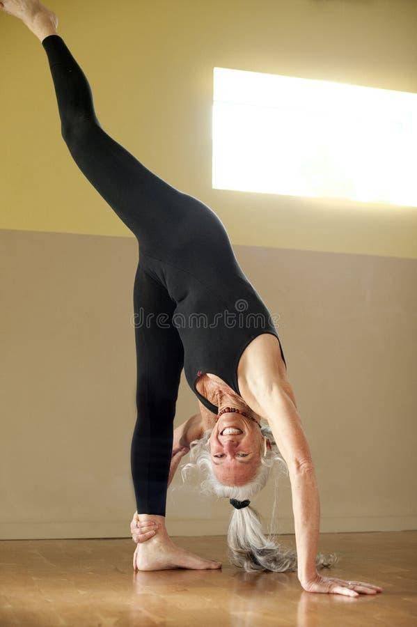 Donna maggiore di yoga nelle spaccature levantesi in piedi fotografia stock