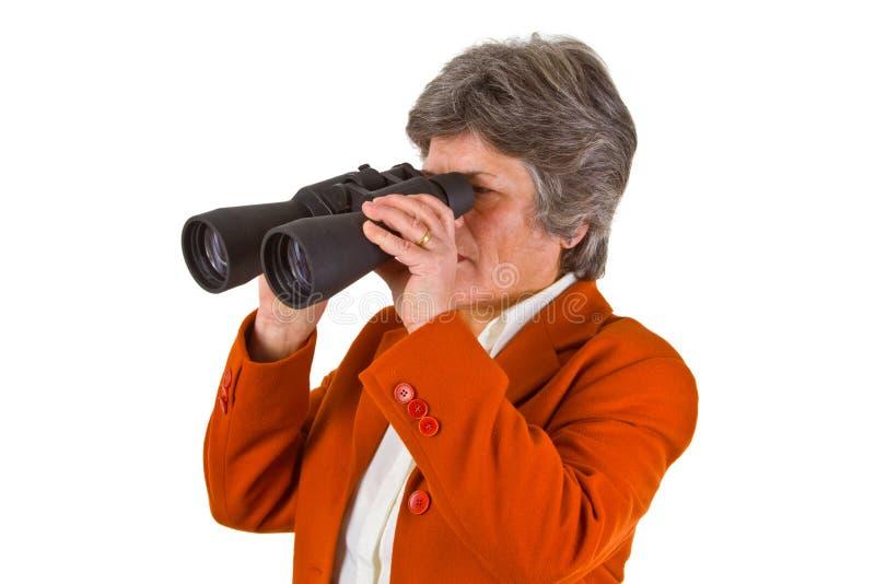 Donna maggiore femminile di affari con il binocolo fotografia stock