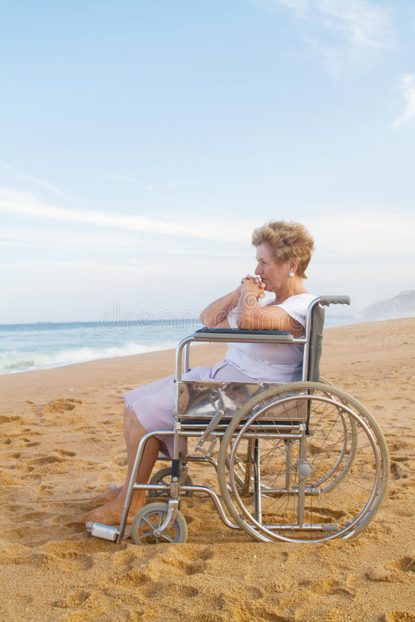 Donna maggiore invalida sulla spiaggia immagini stock