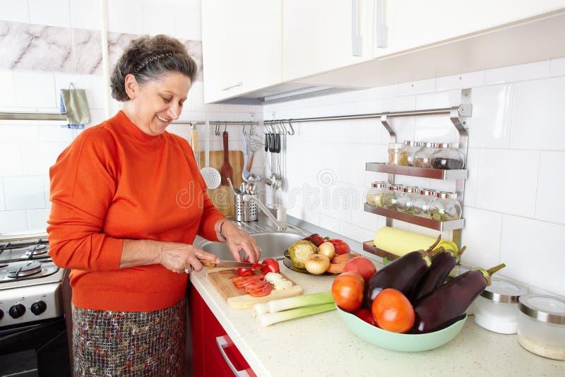 Donna maggiore nella cucina immagini stock