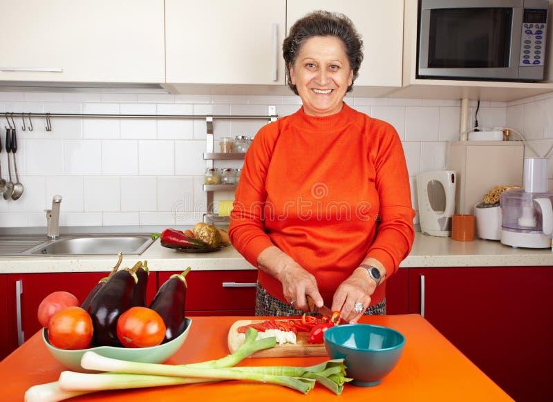 Donna maggiore nella cucina immagine stock