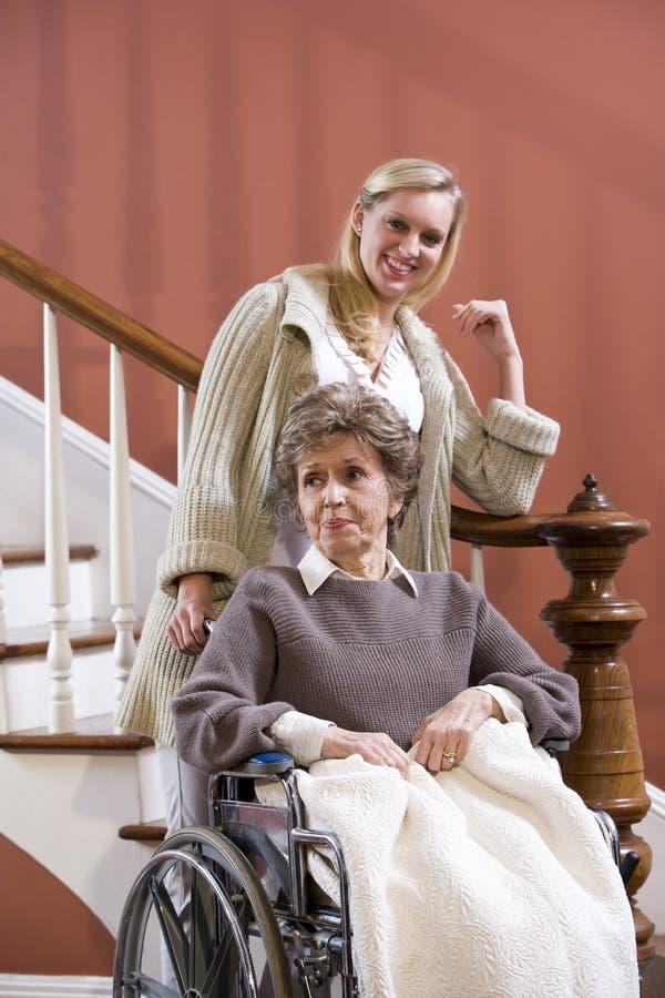 Donna maggiore in sedia a rotelle nel paese con l'infermiera immagini stock