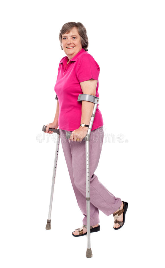 Donna maggiore sorridente che cammina con le grucce immagini stock