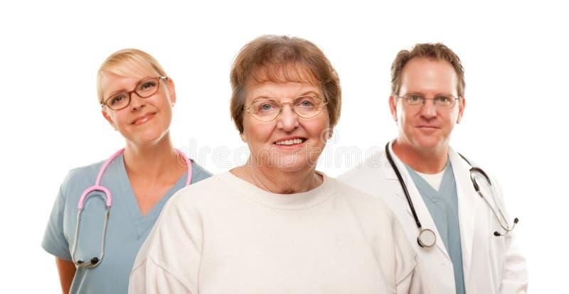 Donna maggiore sorridente con il medico e l'infermiera immagini stock libere da diritti