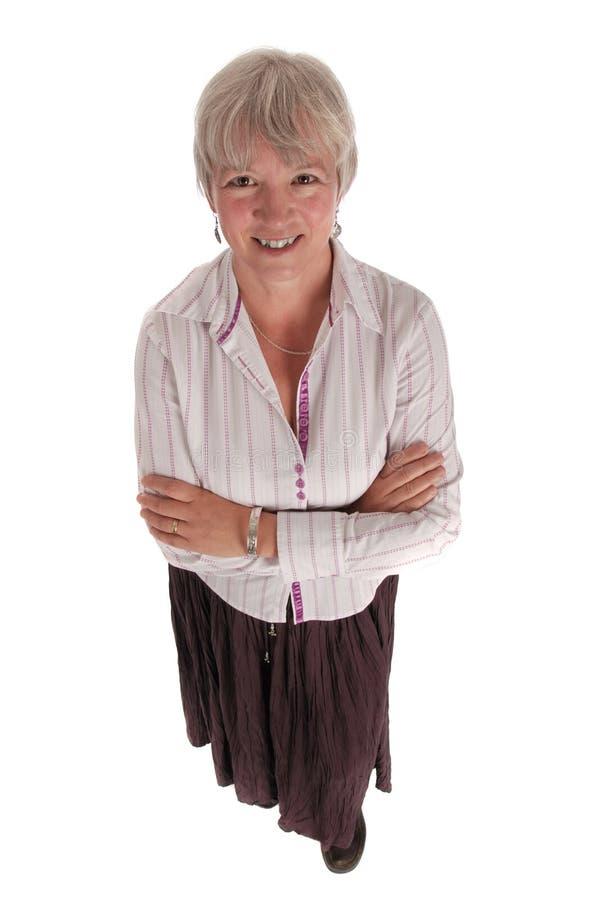Donna maggiore sorridente di affari con le braccia piegate immagini stock
