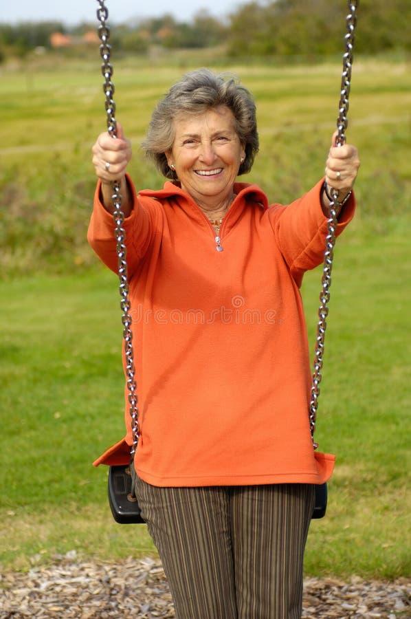 Donna maggiore su un swinger fotografie stock libere da diritti
