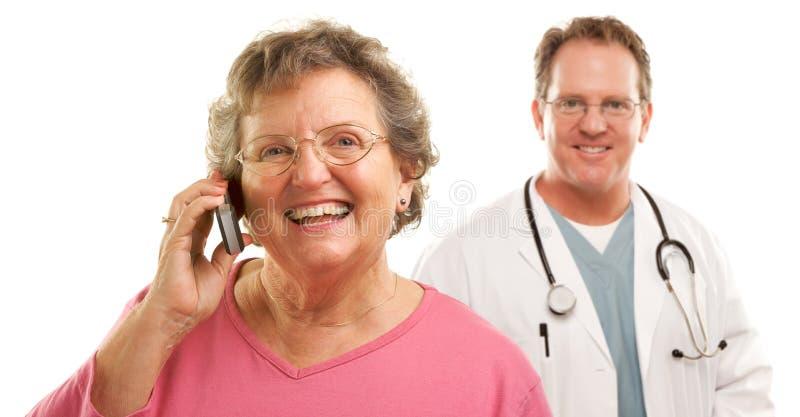 Donna maggiore sul telefono delle cellule con il dottore maschio Behind immagine stock
