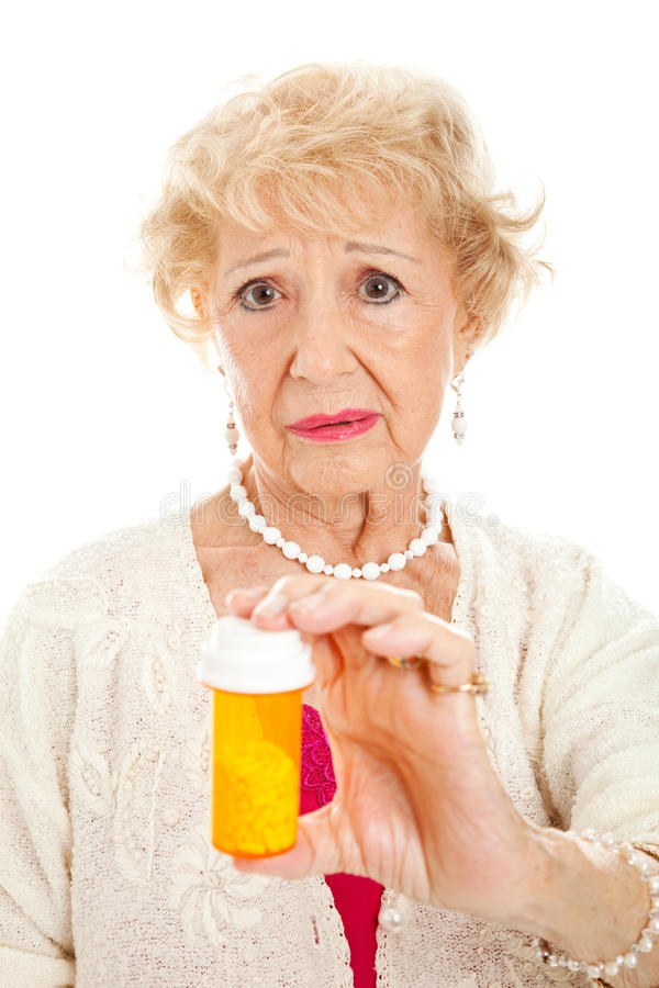 Donna maggiore triste con le pillole immagine stock