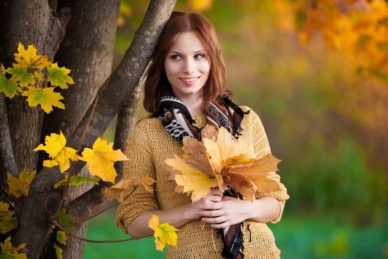 Donna in maglione beige con le foglie immagini stock libere da diritti