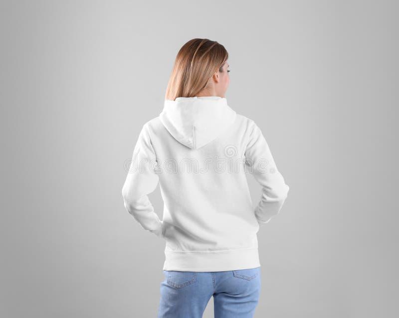 Donna in maglione di maglia con cappuccio su fondo leggero immagini stock libere da diritti