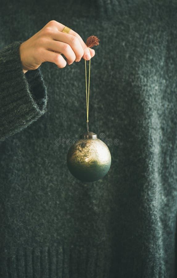 Donna in maglione grigio che giudica palla dorata decorativa disponibila fotografia stock