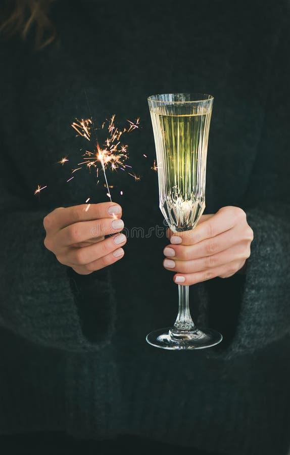 Donna in maglione grigio che tiene le stelle filante e vetro di champagne fotografie stock libere da diritti