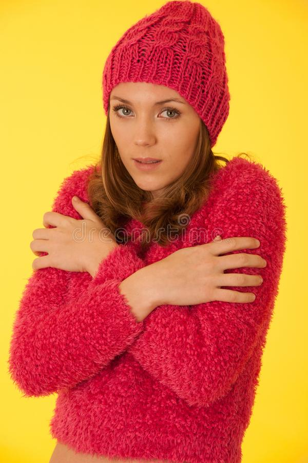 Donna in maglione rosa e cappello tricottato rosa che gesturing freddo sopra fondo giallo fotografia stock libera da diritti
