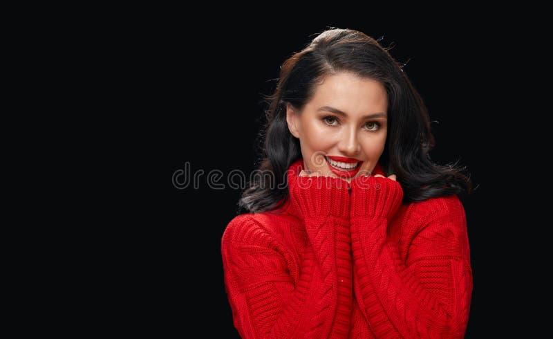 Donna in maglione rosso su fondo nero immagini stock