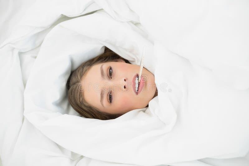 Donna malata che si trova nell'ambito della copertura sul suo letto nella camera da letto fotografia stock libera da diritti