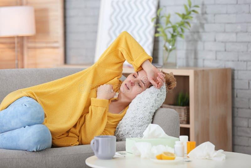 Donna malata che soffre dal freddo sul sofà immagini stock libere da diritti