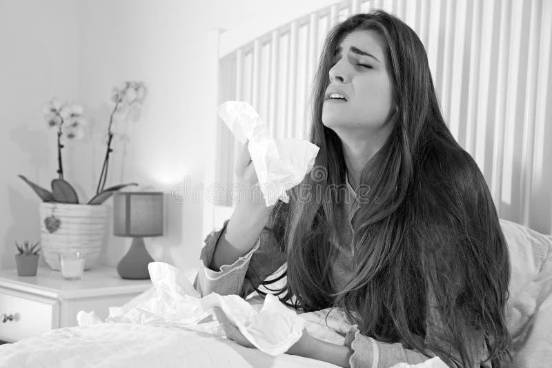 Donna malata che tiene molti fazzoletti che si siedono a letto fotografia stock