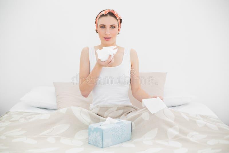 Donna malata che tiene un fazzoletto che si siede sul suo letto fotografie stock libere da diritti