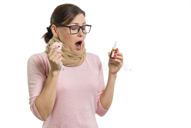 Donna malata che tiene un fazzoletto e uno spray nasale Fondo bianco, isolato immagini stock