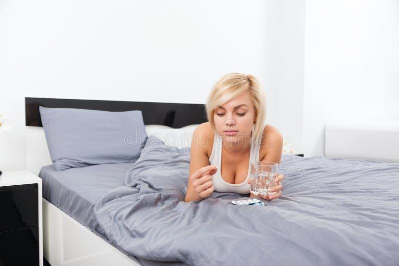 Donna malata con il pacchetto delle pillole che si trovano sul letto fotografia stock