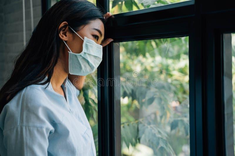 Donna malata di quarantena del coronavirus che guarda attraverso la finestra e indossa una maschera per la protezione mentre si r immagini stock