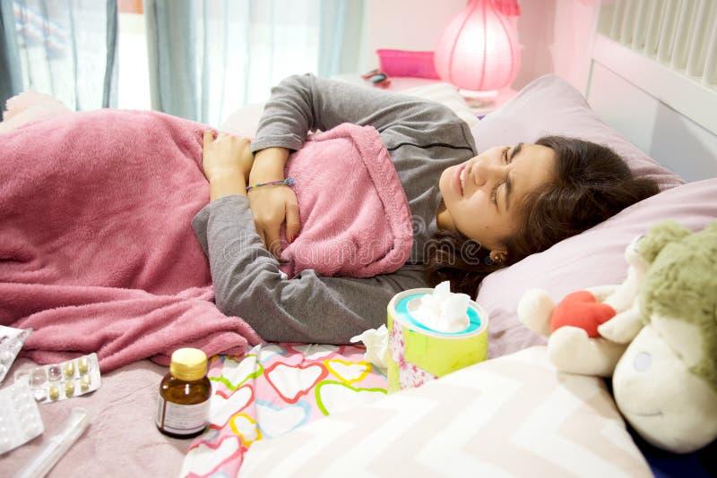 Donna malata ispana a letto con i crampi ed il dolore mestruale fotografie stock