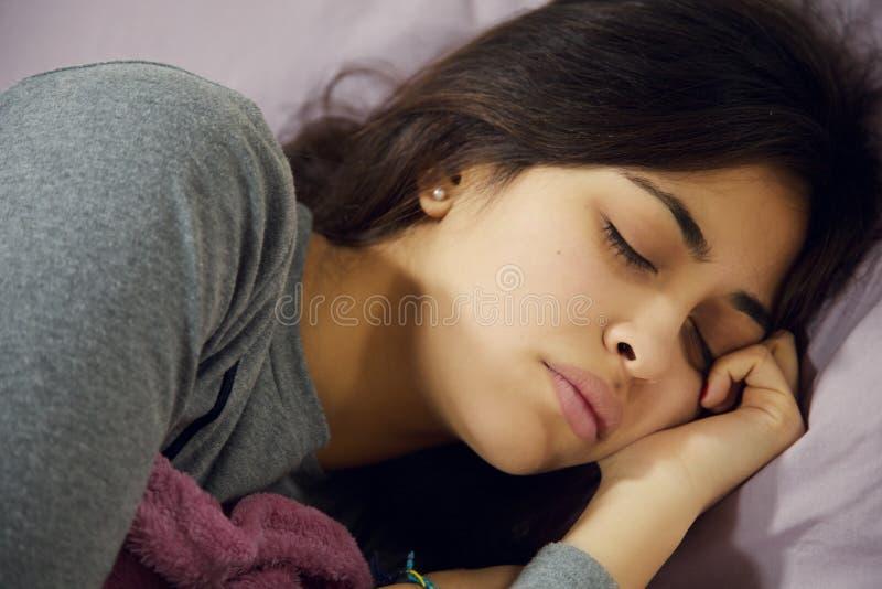 Donna malata ispana a letto con il sonno di influenza e di emicrania fotografia stock libera da diritti