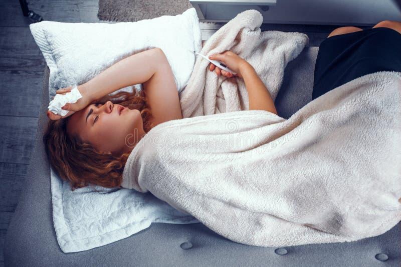 Donna malata a letto con un termometro immagini stock