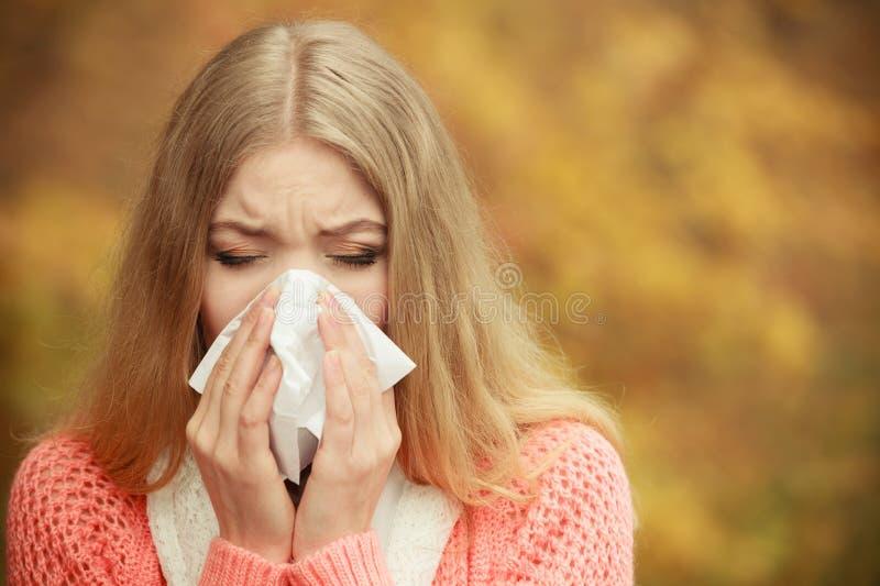 Donna malata malata nel parco di autunno che starnutisce nel tessuto immagini stock