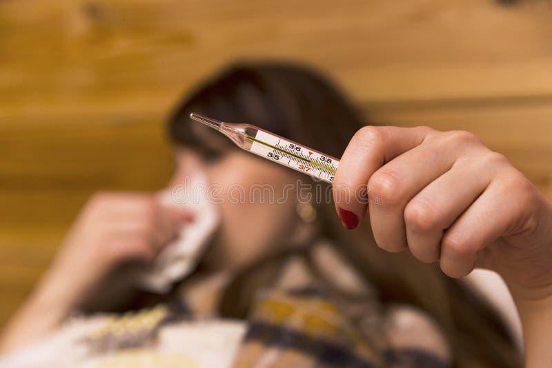 Donna malata nel suo letto che esamina un termometro clinico fotografie stock libere da diritti