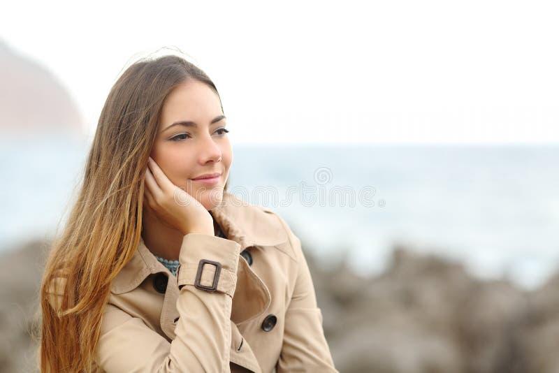 Donna malinconica bella che pensa nell'inverno sulla spiaggia immagine stock