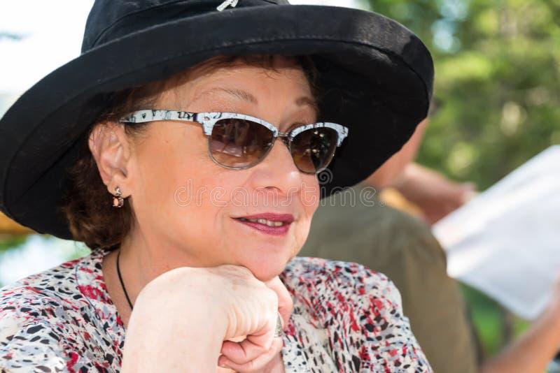Donna matura alla moda in black hat e vetri fotografia stock