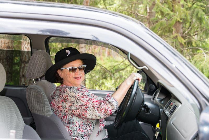 Donna matura alla moda che conduce automobile fotografie stock libere da diritti