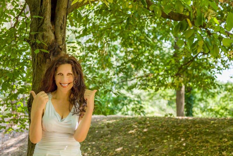 Donna matura allegra che mostra i pollici su fotografia stock