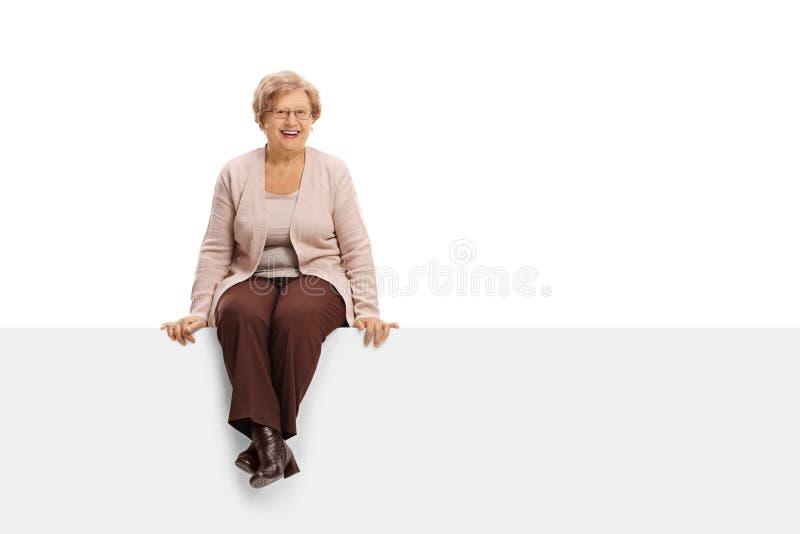 Donna matura allegra che si siede su un pannello immagine stock