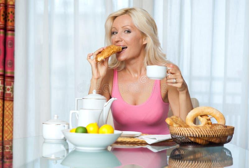 Donna matura attraente alla prima colazione fotografie stock