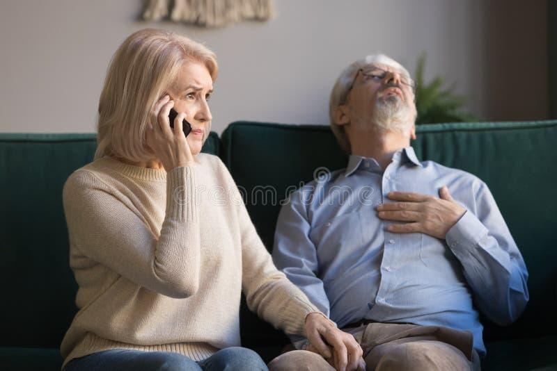 Donna matura che chiama emergenza, uomo dai capelli grigio che ha attacco di cuore fotografie stock libere da diritti