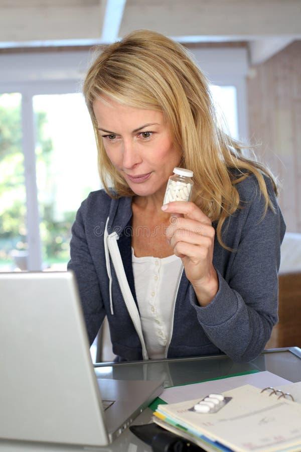 Donna matura che controlla la composizione nel farmaco su Internet fotografie stock
