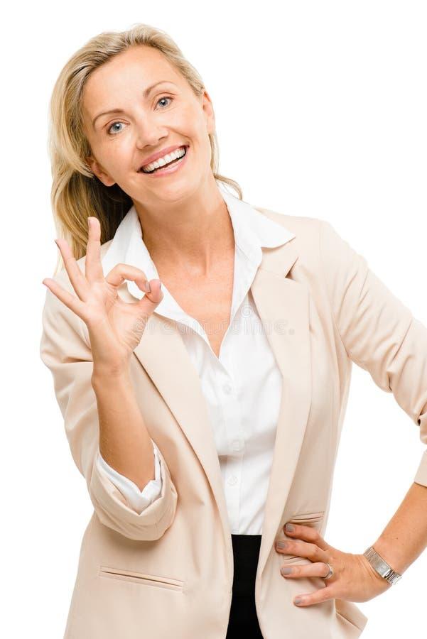 Donna matura che dà segno giusto isolato su fondo bianco immagine stock